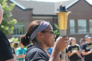 Torch bearer holds torch at ceremony.