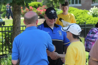 Officer greets athletes after ceremony.